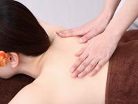 整骨院でハンズオンセラピーを受ける女性